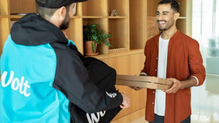 Ein Wolt-Lieferant übergibt einem Kunden eine Pizza